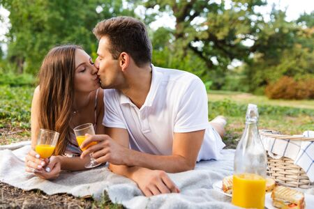 Smiling young couple spending good time together, having picnic at the park, kissing, toasting Stock Photo