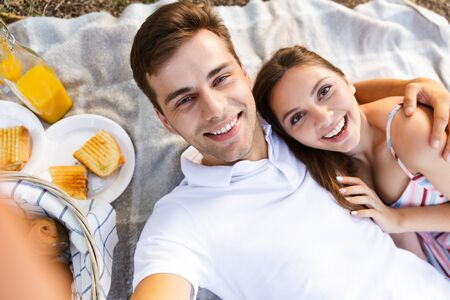 Happy young couple spending good time together, having picnic at the park, taking a selfie
