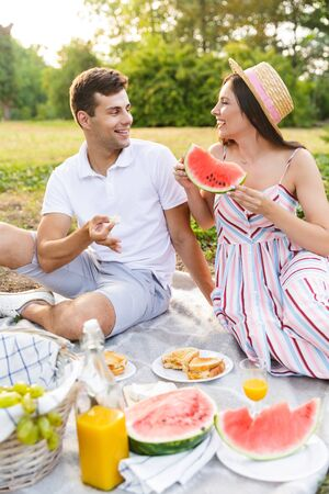 Smiling young couple spending good time together, having picnic at the park Stock Photo