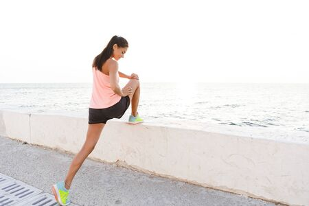 Photo of runner woman 20s in tracksuit stretching legs during doing sports at seaside
