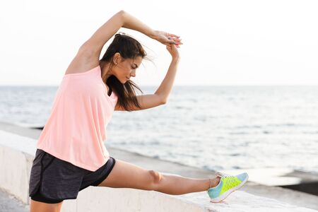 Photo of athletic woman 20s in tracksuit stretching her body during workout at seaside