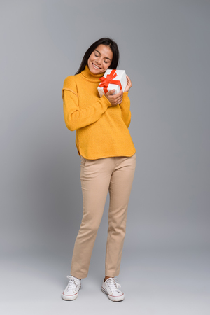 Image of a happy excited woman posing isolated over grey wall background holding box surprise present.