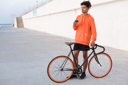 Image of a young sports guy outdoors on the beach with bicycle holding coffee.