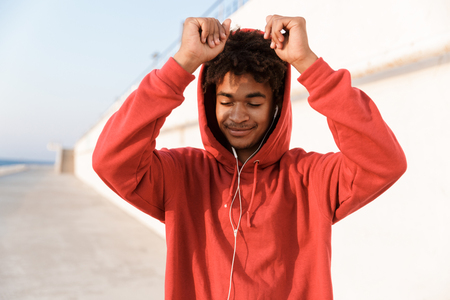 Image of a young sports african guy outdoors on the beach listening music.