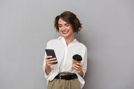 Photo of european woman 20s holding takeaway coffee and using cell phone isolated over gray background