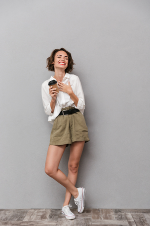 Full length image of beautiful woman 20s smiling and holding takeaway coffee isolated over gray background Stock Photo