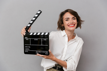 Photo of caucasian woman 20s smiling and holding black clapperboard isolated over gray background