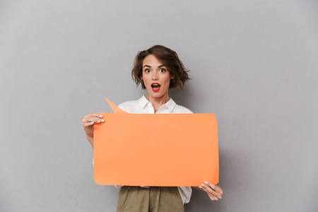Portrait of an excited young woman standing isolated over gray background, showing blank speech bubble Фото со стока