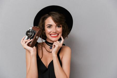 Foto de hermosa mujer de 20 años con vestido negro y sombrero sosteniendo una cámara retro aislada sobre fondo gris Foto de archivo