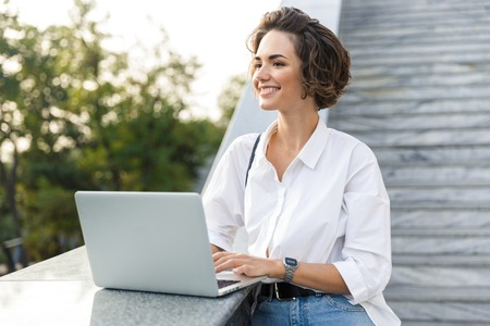 Picture of young cute beautiful woman walking outdoors using laptop computer. 版權商用圖片