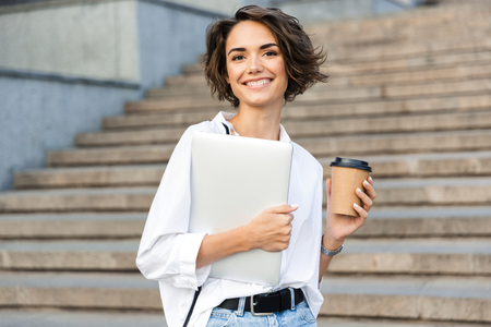 Photo of young cute beautiful woman walking outdoors holding laptop computer holding coffee.