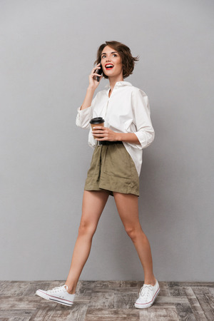 Full length image of gorgeous girl 20s holding takeaway coffee and talking on smartphone isolated over gray background