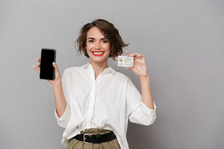 Photo of happy woman 20s holding mobile phone and credit card isolated over gray background Stock Photo