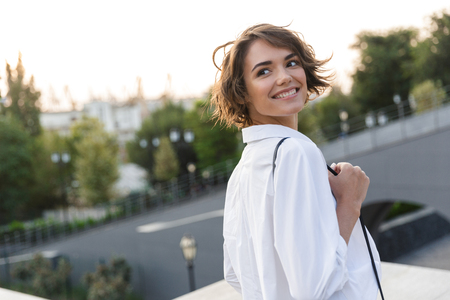 Smiling young woman walking outdoors, looking away Stockfoto