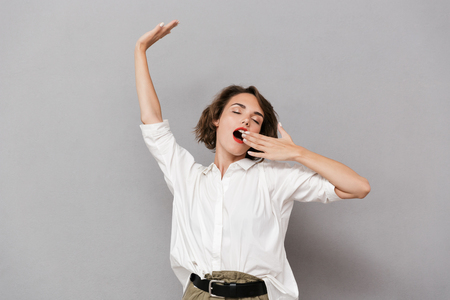 Portrait of a smiling young woman standing isolated over gray background, stretching her arms, yawning