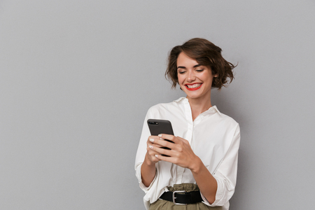 Photo of caucasian woman 20s smiling and holding mobile phone isolated over gray background