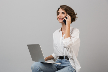 Image of young business woman posing isolated over grey wall background sitting on stool using laptop computer talking by phone.