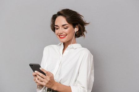 Photo of adorable woman 20s listening to music on smartphone via earphones isolated over gray background