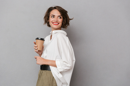 Photo of beautiful woman 20s smiling and holding takeaway coffee isolated over gray background