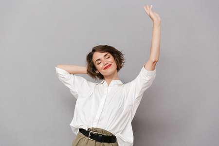Portrait of a smiling young woman standing isolated over gray background, stretching her arms