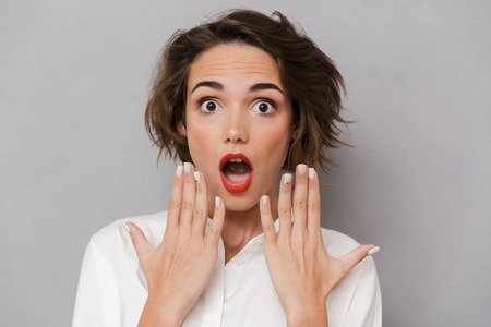 Portrait of a shocked young woman standing isolated over gray background, looking at camera, covering mouth Stock Photo - 112333538
