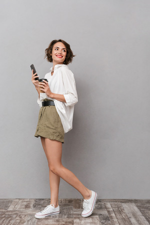 Full length image of brunette girl 20s holding takeaway coffee and using smartphone isolated over gray background
