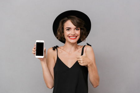 Photo of attractive woman 20s wearing black dress and hat holding smartphone isolated over gray background Stock Photo