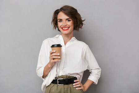 Photo of gorgeous woman 20s smiling and holding takeaway coffee isolated over gray background Stock Photo