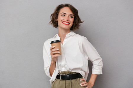 Photo of positive woman 20s smiling and holding takeaway coffee isolated over gray background Stock Photo