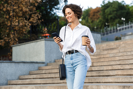 Photo of young cute beautiful woman walking on the street using mobile phone holding coffee.
