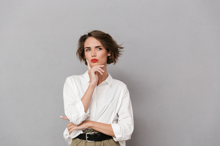 Portrait of a pensive young woman dressed in white shirt standing isolated over gray background, looking away