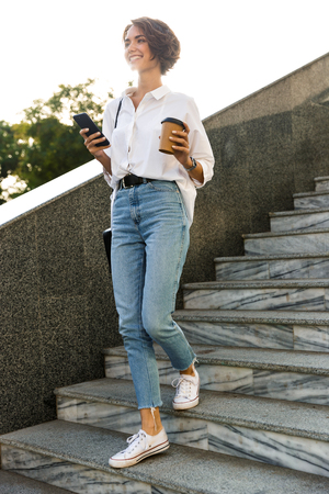Smiling young woman walking downstairs at the street, using mobile phone, drinking coffee Stock Photo