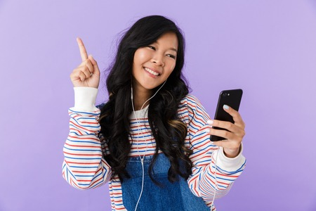 Portrait of a happy young asian woman isolated over violet background listening to music with earphones, holding mobile phone