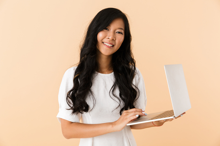 Portrait of a happy young asian woman isolated over beige, using laptop