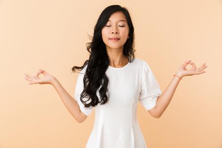Retrato de una mujer asiática joven sonriente aislada sobre fondo beige, meditando, ojos cerrados Foto de archivo