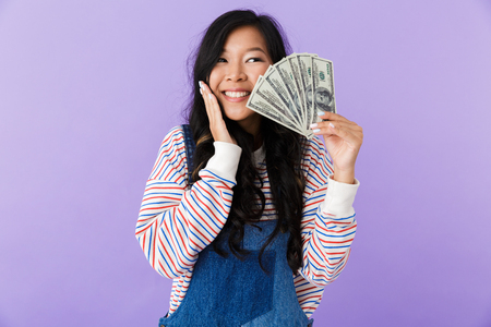 Portrait of an excited young asian woman isolated over violet background showing money banknotes