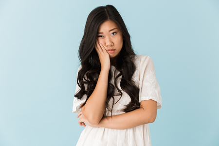 Image of young tired bored asian beautiful woman isolated over blue background. Stockfoto