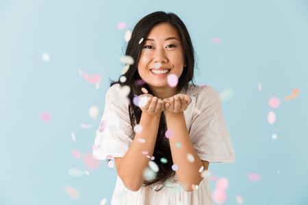 Imagen de mujer emocional joven asiática aislada sobre fondo azul sobre confeti. Foto de archivo