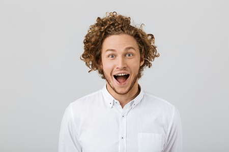 Portrait of a surprised young man with curly hair isolated over white background, open mouth 스톡 콘텐츠 - 112726181