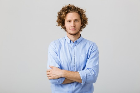Portrait of a handsome young man wearing shirt standing isolated over gray background, arms folded