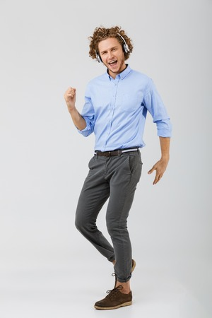 Full length portrait of a cheerful young man with curly hair isolated over white background, listening to music with headphones, dancing Stockfoto - 112726257