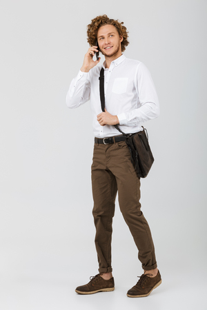 Full length portrait of a smiling businessman dressed in shirt isolated over white background, talking on mobile phone 写真素材