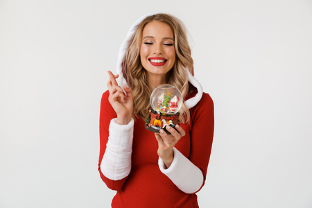 Portrait of a wishful blonde woman dressed in red New Year costume standing isolated over white background, holding snowball, fingers crossed