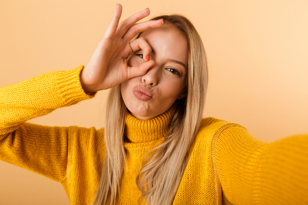 Portrait of a pretty young woman dressed in sweater standing isolated over yellow background, taking a selfie, showing ok