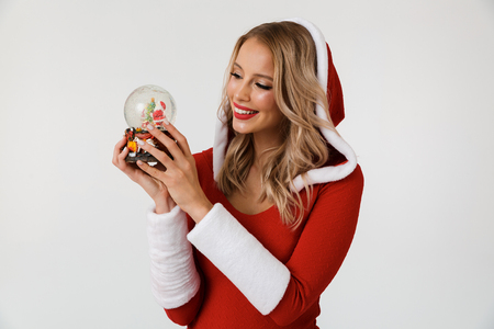 Portrait of a smiling blonde woman dressed in red New Year costume standing isolated over white background, holding snowball