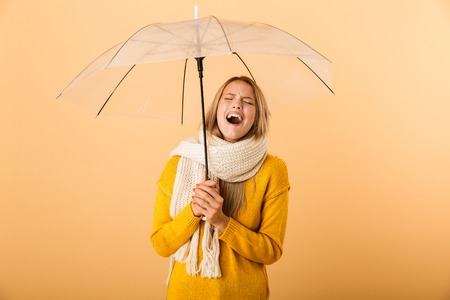 Photo of a cry screaming woman wearing scarf holding umbrella posing isolated over yellow wall background.