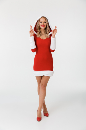 Full length portrait of a smiling blonde woman dressed in red New Year costume standing isolated over white background, holding fingers crossed for good luck Stok Fotoğraf - 112901560