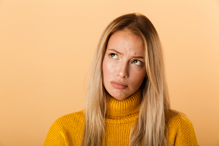 Close up portrait of an upset young woman dressed in sweater standing isolated over yellow background Foto de archivo - 112901564