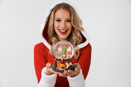 Portrait of a joyful blonde woman dressed in red New Year costume standing isolated over white background, holding snowball