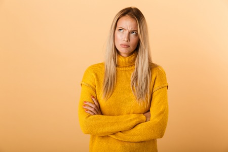 Portrait of an upset young woman dressed in sweater standing isolated over yellow background, holding arms folded, looking away Stock Photo